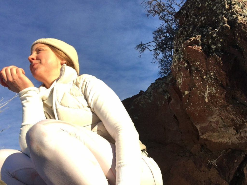 "Woman in white squatting outdoors | ""A Lifetime of Hiding My Thighs"" by Emily Wishall 